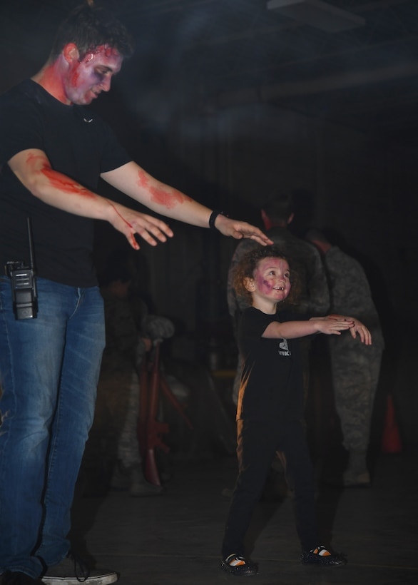 Kariana Henry, three years, shows off her zombie walk to an Operation Iron Zombie volunteer October 31, 2018, on Grand Forks Air Force Base. Iron Zombie was a Halloween-themed readiness exercise, with actors dressing up in spooky costumes to scare Airmen participating in the event. (U.S. Air Force photo by Airman 1st Class Elora J. Martinez)