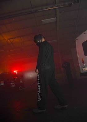 Airman 1st Class Jacob Westafor, 319th Logistics Readiness Squadron fire truck maintenance apprentice, lurks through a vehicle barn in costume for Operation Iron Zombie October 31, 2018, on Grand Forks Air Force Base. Westafor and several other volunteers dressed like scary characters for the Halloween-themed readiness exercise, acting as distractions for Airmen participating through the event which tested important skills to include problem-solving, and self-aid and buddy care. (U.S. Air Force photo by Airman 1st Class Elora J. Martinez)