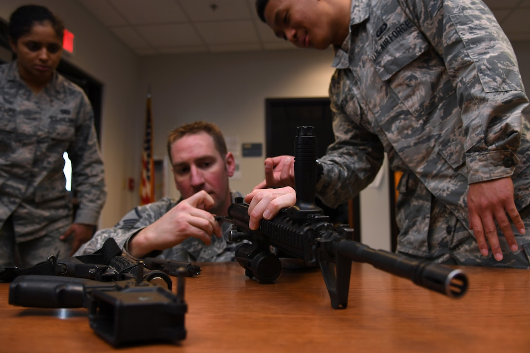 Master Sgt. Dustin Dallas, 319th Contracting Flight superintendent, assembles an M4 carbine with the help of his fellow 319 CONF team members during Operation Iron Zombie October 31, 2018, on Grand Forks Air Force Base, North Dakota. Weapons assembly and disassembly was one of the seven stations included in the Halloween-themed readiness exercise, with the other stations focused on important skills to include problem-solving, and self-aid and buddy care. (U.S. Air Force photo by Airman 1st Class Elora J. Martinez)