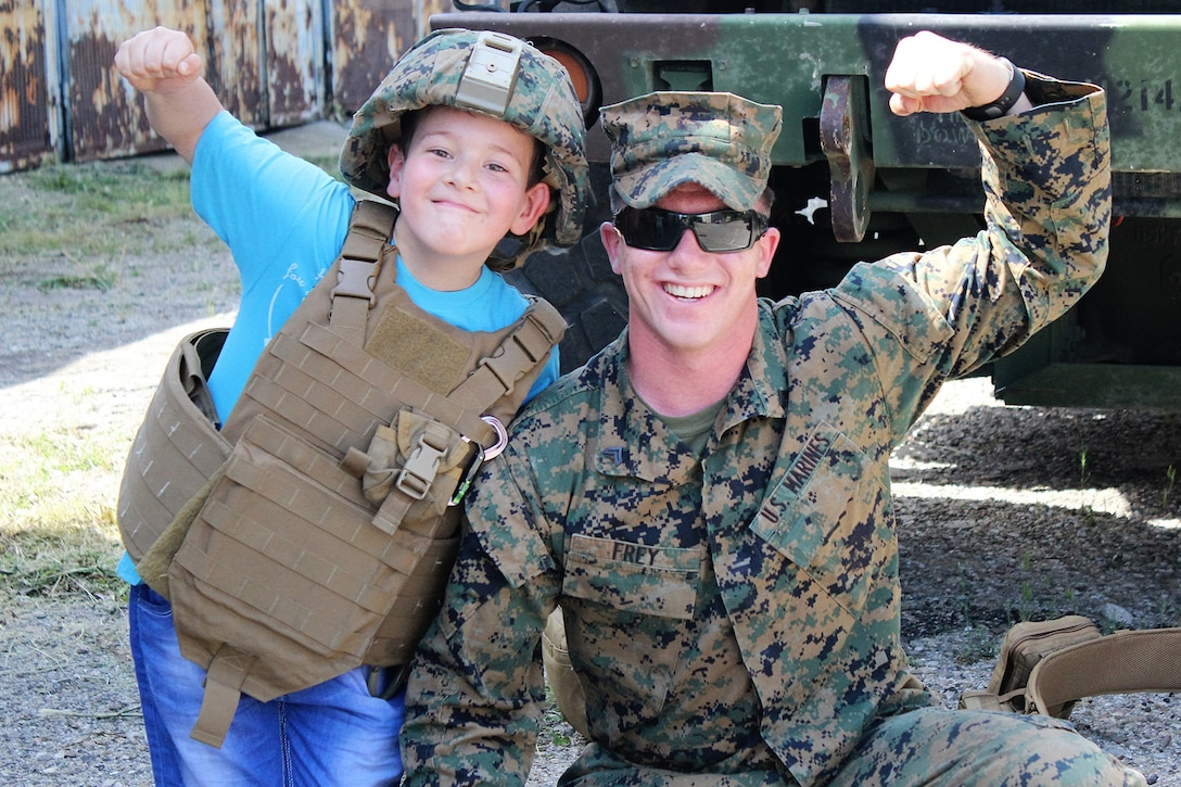 A Marine and child make muscles for the camera