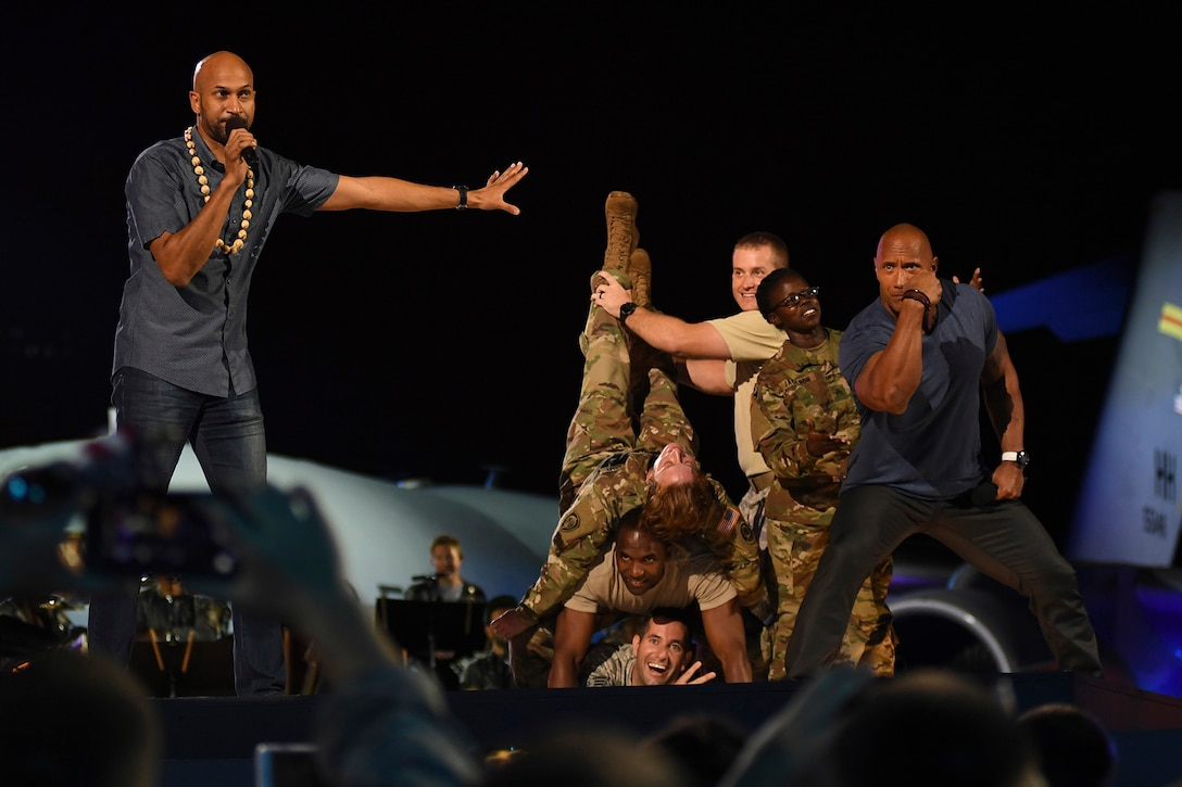 Actors pose on stage with service members