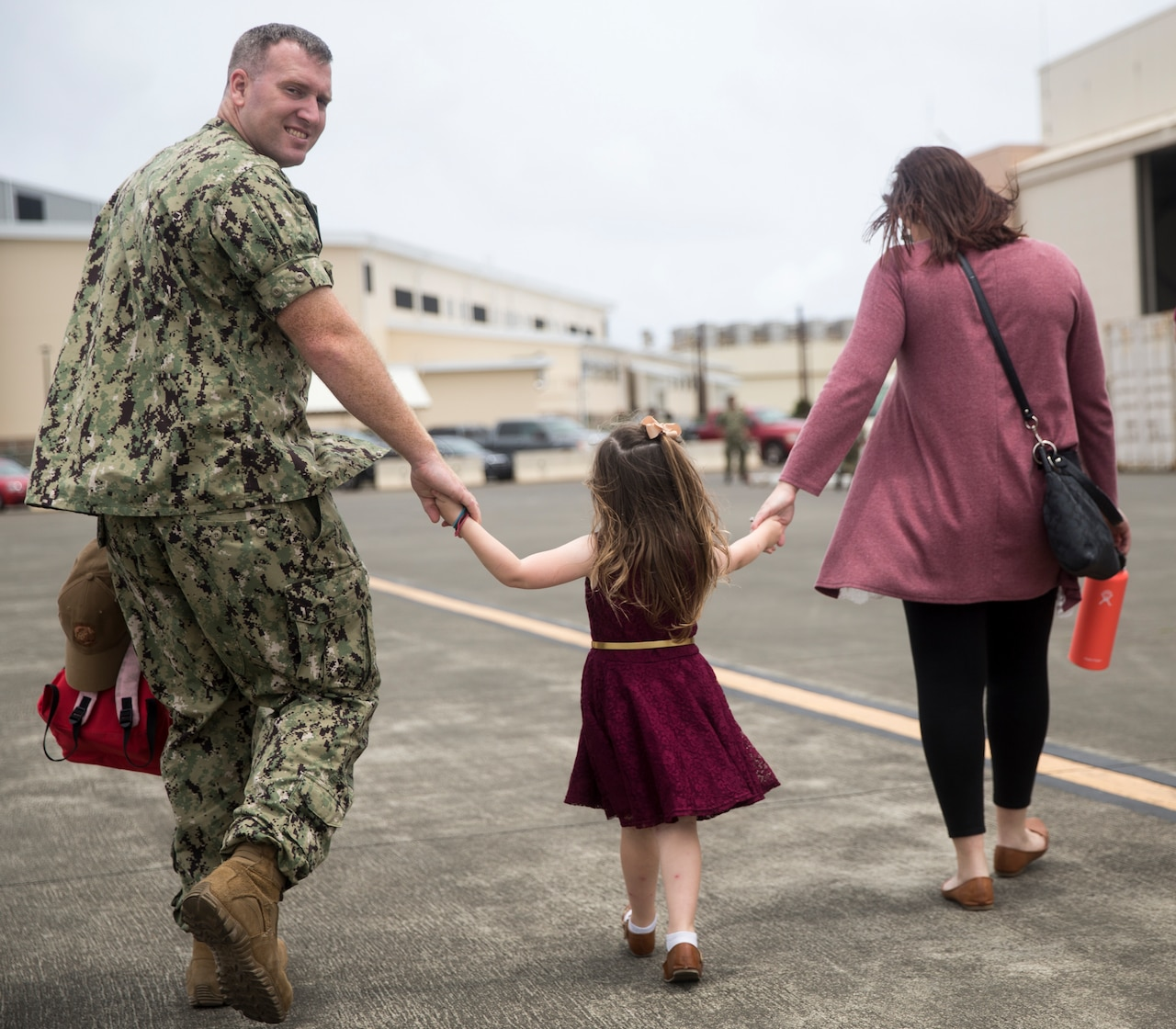 A sailor and his wife hold hands with their daughter