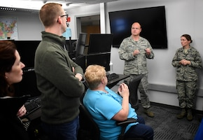 Maj. Chris Higgins and Lt. Col. Laura Madden, 12th Operational Weather Flight, explains their weather prediction roles to civilian employers visiting Scott Air Force Base, Illinois on October 13, 2018. The event was Boss Day and employers were the guests.    They learned that the Air Force has always been the backup agency for the Storm Prediction Center (SPC). Historically, it was on May 1, 2009 that the mission came to the 15th Operational Weather Squadron.   The SPC handed off support to Airmen like Maj. Higgins on 26 March that year, and even though SPC has a lot of other weather speciality products they produce, the ones that 12 OWF are in charge of are the convective outlooks days and weather watches. SPC is located in Norman, Oklahoma, so if they ever have to shelter for a tornado the Storm Prediction Center backup team is called in to take over. Maj. Higgins spent time on the phones with weather managers in various states during the event. Boss Day showed off various areas of the 932nd Airlift Wing and Scott Air Force Base.  (U.S. Air Force photo by Lt. Col. Stan Paregien)