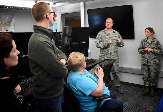 Maj. Chris Higgins and Lt. Col. Laura Madden, 12th Operational Weather Flight, explains their weather prediction roles to civilian employers visiting Scott Air Force Base, Illinois on October 13, 2018. The event was Boss Day and employers were the guests.  