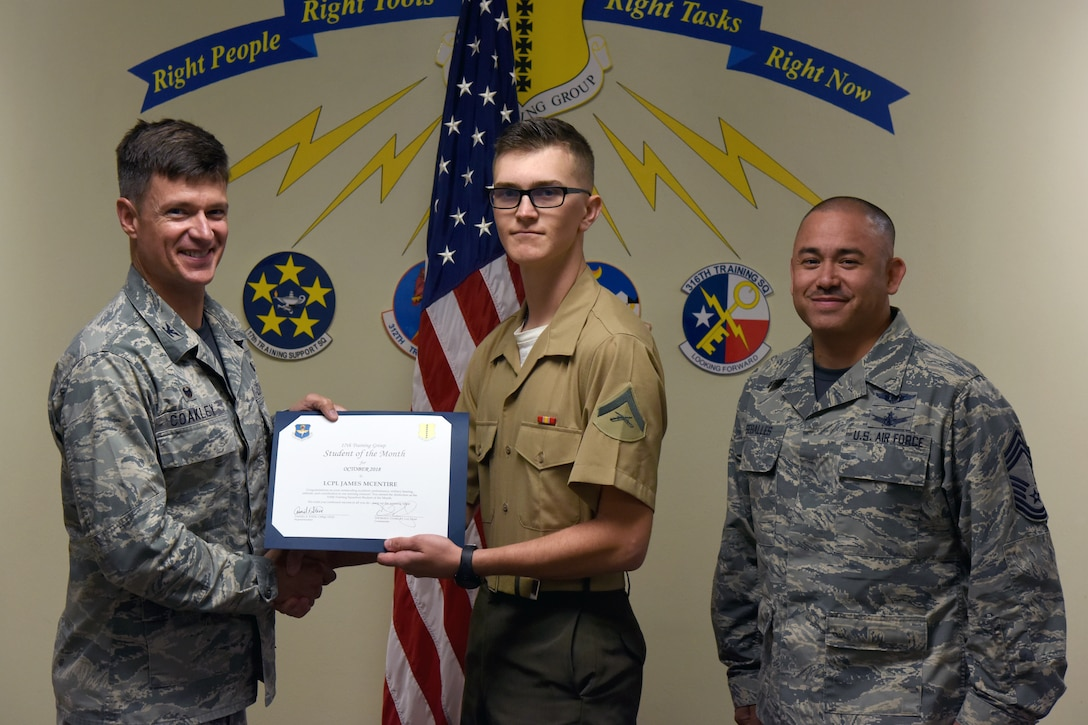 U.S. Air Force Col. Thomas Coakley, 17th Training Group commander, presents the 316th Training Squadron Student of the Month award to Lance Cpl. James Mcentire, 316th TRS student, at Brandenburg Hall on Goodfellow Air Force Base, Texas, Nov. 2, 2018. The 316th TRS's mission is to conduct U.S. Air Force, U.S. Army, U.S. Marine Corps, U.S. Navy and U.S. Coast Guard cryptologic, human intelligence and military training. (U.S. Air Force photo by Airman 1st Class Zachary Chapman/Released)