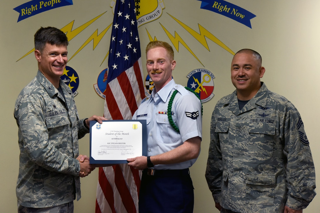 U.S. Air Force Col. Thomas Coakley, 17th Training Group commander, presents the 315th Training Squadron Student of the Month award to Airman 1st Class Dylan Heeter, 315th TRS student, at Brandenburg Hall on Goodfellow Air Force Base, Texas, Nov. 2, 2018. The 315th TRS's vision is to develop combat-ready intelligence, surveillance and reconnaissance professionals and promote an innovative squadron culture and identity unmatched across the U.S. Air Force. (U.S. Air Force photo by Airman 1st Class Zachary Chapman/Released)
