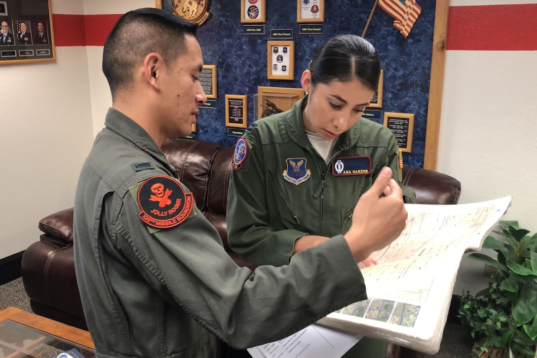 Two Air Force missileers look over a map.