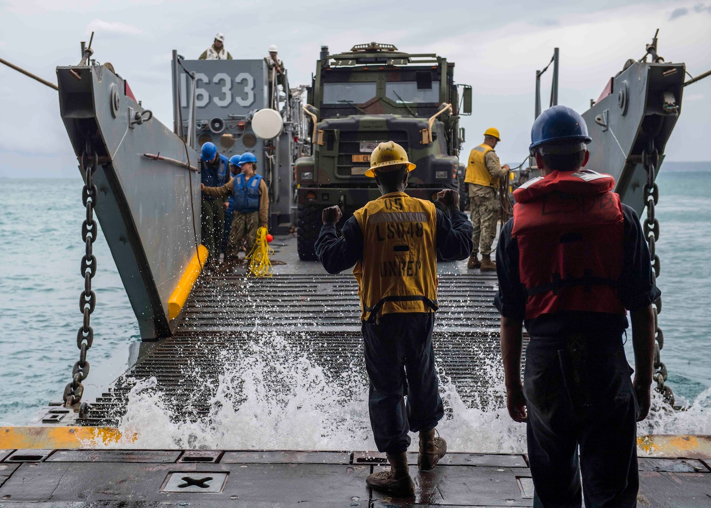 OKINAWA, Japan (Oct. 29, 2018) Boatswain's Mate 3rd Class Nayyaamunhotep Stubbs signals the Landing Craft, Utility (LCU) 1633 to approach the well deck of the amphibious dock landing ship USS Ashland (LSD 48) to receive equipment in preparation to conduct Defense Support to Civil Authorities (DSCA) efforts. Sailors and Marines from Ashland, part of the Wasp Amphibious Ready Group and 31st Marine Expeditionary Unit team, are preparing to provide Department of Defense support to the Commonwealth of the Northern Mariana Islands' civil and local officials as part of the FEMA-supported Typhoon Yutu recovery efforts.
