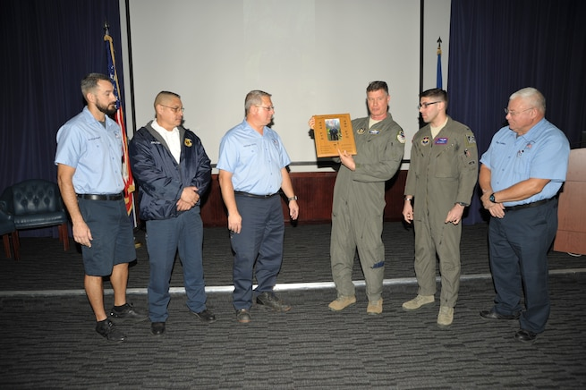 Lt. Col. Lee Glenn and 1st Lt. Nick Donato present a custom plaque to members of the 12th OSS' egress shop