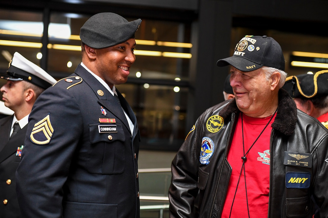 A soldier shares a laugh with a veteran.