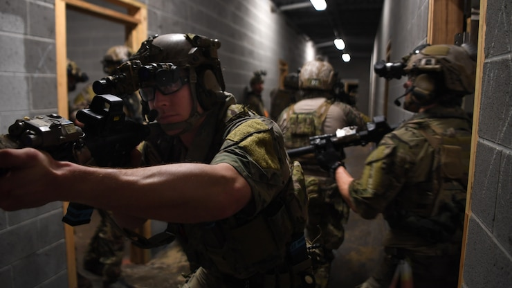 A Team of Special Tactics Candidates clears a hallway in a concrete building during an exercise.