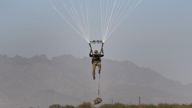 A Special Tactics Operator faces the camera during a parachute landing as his gear bag dangles below him feet from the ground.