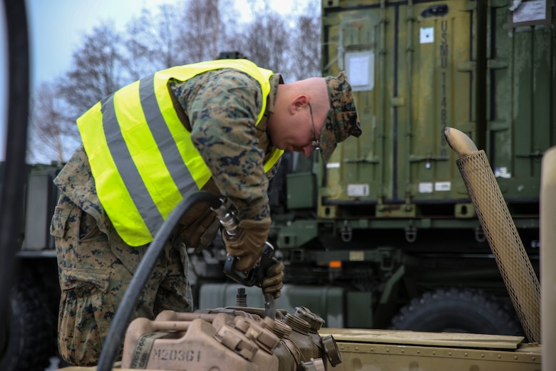 A U.S. Marine with II Marine Support Battalion, II Marine Information Group, refills fuel containers during a convoy operation for Exercise Trident Juncture.