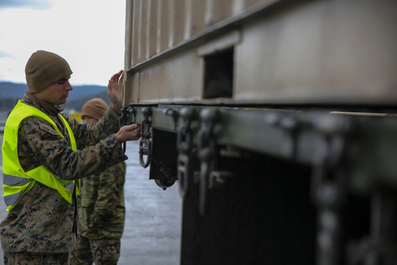 U.S. Marine Lance Cpl. Aaron Slusarczyk, a maintenance mechanic with II Marine Support Battalion, II Marine Information Group, unlocks the hooks on a 7-ton medium tactical vehicle replacement during a convoy operation for Exercise Trident Juncture. Trident Juncture 18 demonstrates II Marine Expeditionary Force's ability to deploy, employ, and redeploy the Marine Air Ground Task Force while improving interoperability with NATO allies and partners. (U.S. Marine Corps photo by Cpl. Patrick Osino)