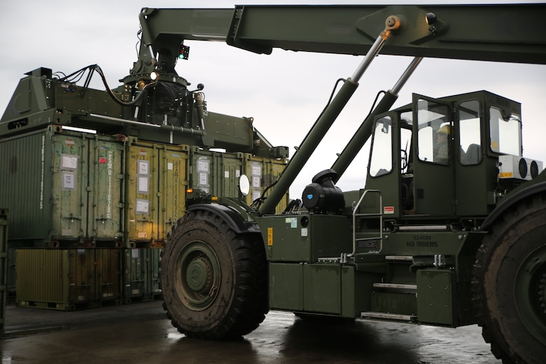 A U.S. Marine with II Marine Support Battalion, II Marine Information Group, offloads containers with supplies to be used for Exercise Trident Juncture 18 in Vaernes, Norway, Nov. 2, 2018. Trident Juncture 18 demonstrates II Marine Expeditionary Force's ability to deploy, employ, and redeploy the Marine Air Ground Task Force while improving interoperability with NATO allies and partners. (U.S. Marine Corps photo by Cpl. Patrick Osino)