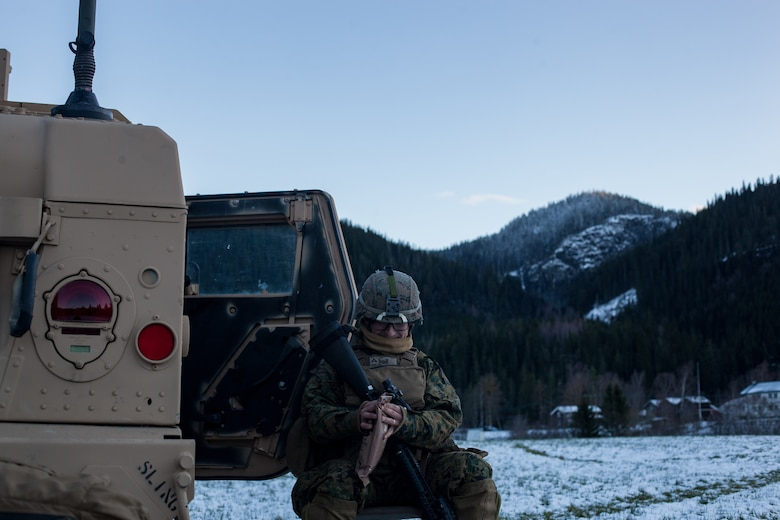 U.S Marine Corps Lance Cpl. William Evans with Bridge Company, 8th Engineer Support Battalion, 2nd Marine Logistics Group-Forward, opens a meal ready to eat beside a Humvee during Exercise Trident Juncture 18 near Voll, Norway, Oct. 29, 2018. The bridge construction enables ground units to complete a gap crossing during the exercise, which is one of the general engineering tasks 2nd MLG provides to the Marine Air-Ground Task Force. Trident Juncture 18 enhances the U.S. and NATO Allies' and partners' abilities to work together collectively to conduct military operations under challenging conditions. (U.S. Marine Corps photo by Lance Cpl. Scott R. Jenkins)