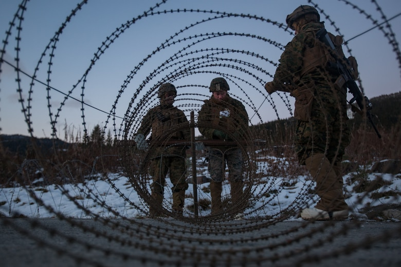 U.S. Marine Corps, Sgt. Michael Wilson, center, with Bridge Company, 8th Engineer Support Battalion, 2nd Marine Logistics Group-Forward, set up concertina wire during security set up before a bridging operation during Exercise Trident Juncture 18 near Voll, Norway, Oct. 29, 2018. The bridge construction enables ground units to complete a gap crossing during the exercise, which is one of the general engineering tasks 2nd MLG provides to the Marine Air-Ground Task Force. Trident Juncture 18 enhances the U.S. and NATO Allies' and partners' abilities to work together collectively to conduct military operations under challenging conditions. (U.S. Marine Corps photo by Lance Cpl. Scott R. Jenkins)