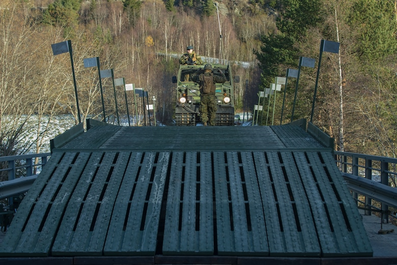 Norwegian military members use a Bandvagn-206 to cross a medium girder bridge as part of Exercise Trident Juncture 18 near Voll, Norway, Oct. 30, 2018. The bridge construction enables ground units to complete a gap crossing during the exercise, which is one of the general engineering tasks 2nd Marine Logistics Group provides to the Marine Air-Ground Task Force. Trident Juncture 18 enhances the U.S. and NATO Allies' and partners' abilities to work together collectively to conduct military operations under challenging conditions. (U.S. Marine Corps photo by Lance Cpl. Scott R. Jenkins)