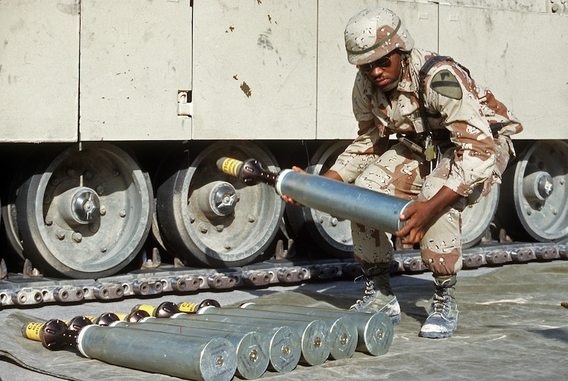 A service member lifts a metal round in front of a wheeled vehicle.