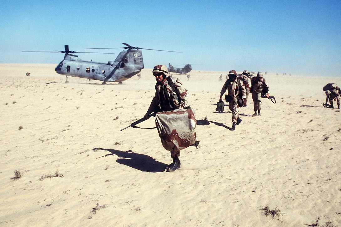 Marines run over sandy terrain near a helicopter.