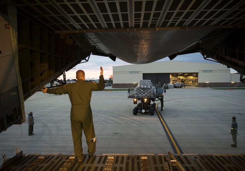 A loadmaster from the 337th Airlift Squadron directs an oncoming vehicle for loading cargo onto a C-5 Galaxy Nov. 2, 2018 at Grissom Air Reserve Base, Indiana. The 84,700 pounds of cargo contained nearly 500,000 meals that are headed for Afghanistan. (U.S. Air Force photo/Tech. Sgt. Jami K. Lancette)