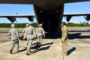 """Members of the 36th Aeromedical Evacuation Squadron, which is a part of the 403rd Wing at Keesler Air Force Base, Mississippi, use a litter to carry an """"injured"""" patient to a C-130J for aeromedical evacuation during an exercise Nov. 4, 2018, at Camp Shelby, Mississippi. The 403rd Wing participated in an exercise during the November 2018 Unit Training Assembly to test their ability to survive and operate in a deployed environment. (U.S. Air Force photo by Tech. Sgt. Ryan Labadens)"""