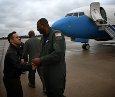 """Lt. Col. Brandon Lorton, 73rd Airlift Squadron pilot, congratulates Col. Esteban  """"Esty"""" Ramirez, the vice commander of the 932d Airlift Wing, as he exits his last C-40 flight at the 932nd Airlift Wing Nov. 4, 2018, at Scott Air Force Base, Ill. The colonel will be transferring to the U.S Transportation Command.  The wing flies the C-40C aircraft and is the premier distinguished visitor airlift operation in the Air Force Reserve Command. With over 1,000 members, the wing equips trains and organizes a ready force of Citizen Airmen to support and maintain all facets of air base operations involving infrastructure and security. (U.S. Air Force photo by Lt. Col. Stan Paregien)"""