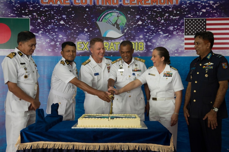 Rear Adm. Joey Tynch, Commander Task Force 73, Capt. Ann McCann, deputy commodore of Destroyer Squadron 7, Rear Adm. M Abu Ashraf, Commander, Chattogram Naval Area, and Rear. Adm. Mohammad Nazmul Hassan, Commander, Bangladesh Navy Fleet share a laugh during the opening ceremony cake-cutting at Cooperation Afloat Readiness and Training (CARAT) 2018. CARAT Bangladesh 2018 marks the 24th iteration of the maritime exercise series and reflects the strong and mature partnership between the U.S. and Bangladesh Navy.