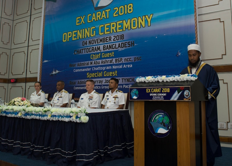 Rear Adm. Joey Tynch, Commander Task Force 73, Capt. Ann McCann, deputy commodore of Destroyer Squadron 7, Rear Adm. M Abu Ashraf, Commander, Chattogram Naval Area, and Rear. Adm. Mohammad Nazmul Hassan, Commander, Bangladesh Navy Fleet listen to a recitation during the opening ceremony Cooperation Afloat Readiness and Training (CARAT) 2018. CARAT Bangladesh 2018 marks the 24th iteration of the maritime exercise series and reflects the strong and mature
