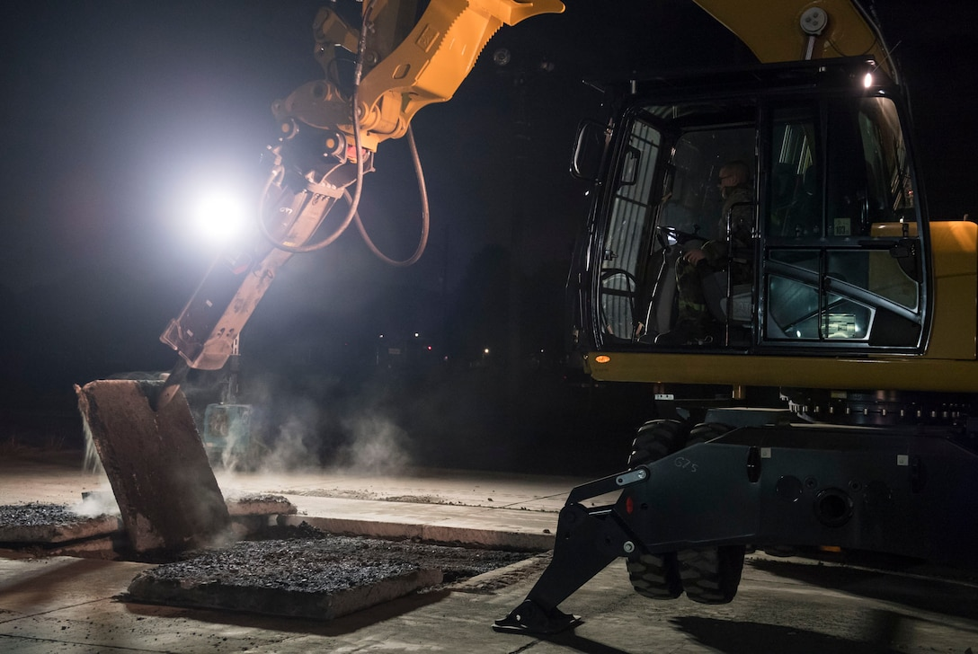 An Airman with the 374th Civil Engineer Squadron runs a wheel excavator to move a piece concrete for Rapid Airfield Damage Repair (RADR) during Exercise Beverly Morning 18-04, at Yokota Air Base, Japan