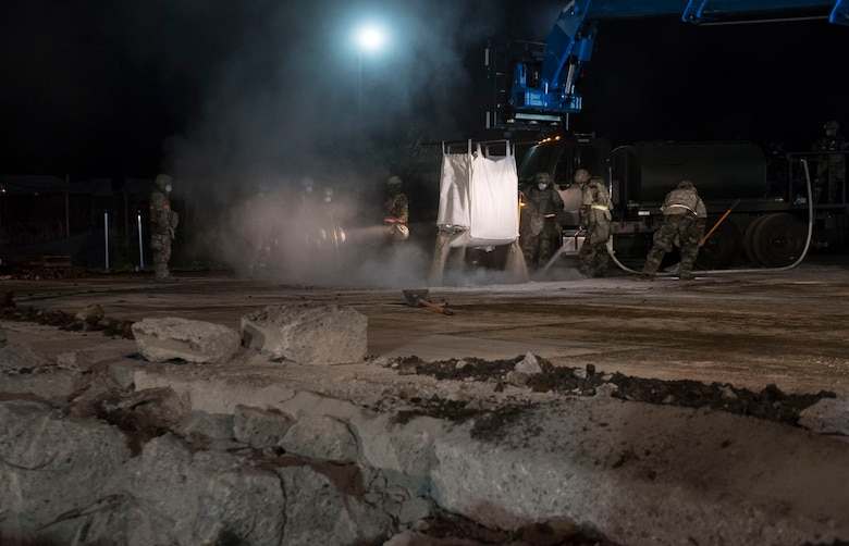 Airmen with the 374th Civil Engineer Squadron fill a crater with water and concrete during Exercise Beverly Morning 18-04, at Yokota Air Base, Japan