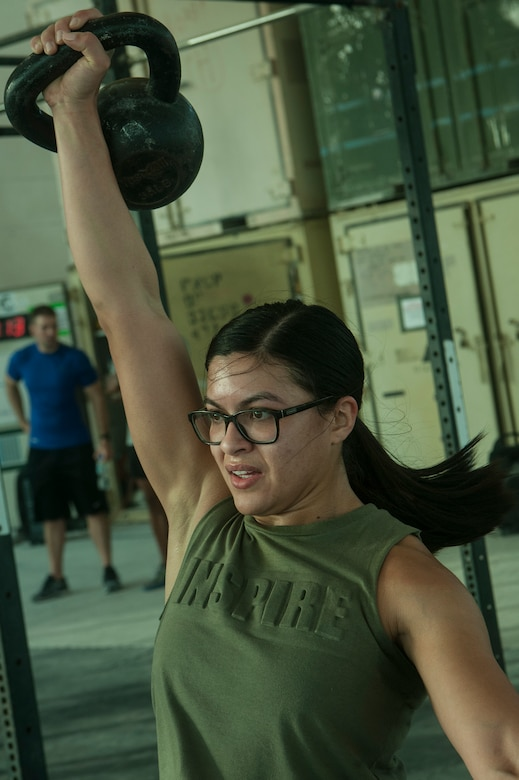 U.S. Air Force Senior Airman Erica Garcia, 379th Expeditionary Logistics Readiness Squadron, lifts a kettle bell during the 2018 EOD 133 Memorial Workout Nov. 4, 2018, at Al Udeid Air Base, Qatar. The event was held in honor of U.S. Army Sgt. James Slape, 430th Explosive Ordnance Company, who was killed by an improvised explosive device Oct. 4, 2018. (U.S. Air Force photo by Tech. Sgt. Christopher Hubenthal)