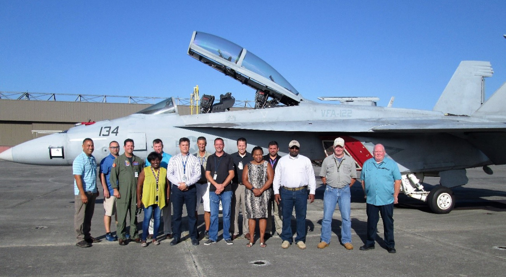 Group photo of males and females standing in front of a jet