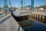 """Oscar,"" a 75-foot Landing Craft Mechanized ship operated by U.S. Navy Sailors assigned to the Navy Boat Docks at Marine Corps Air Station Cherry Point, N.C., gets placed back in the water after undergoing maintenance, Oct. 31, 2018. From top to bottom, the entire ship was refurbished at a commercial boat yard near Beaufort, N.C. From blasting the barnacles off the bottom, to applying multiple coats of paint and primer, to welding any dings and dents the boat has suffered throughout the past year; no blemish was overlooked. (U.S. Marine Corps photo by Lance Cpl. Andrew King)"