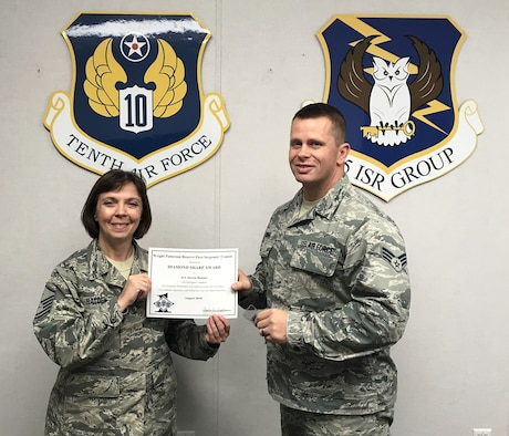 Master Sgt. Angela Hayden, 14th Intelligence Squadron first sergeant, presents the August 2018 Diamond Sharp Award to Senior Airman Steven Bonner, 14th IS, during the October  2018 unit training assembly