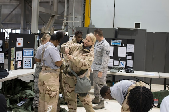 Tech. Sgt. Kathleen Wyatt, 445th Civil Engineer Squadron wing emergency manager, helps a Meadowdale High School student don a chemical warfare suit.