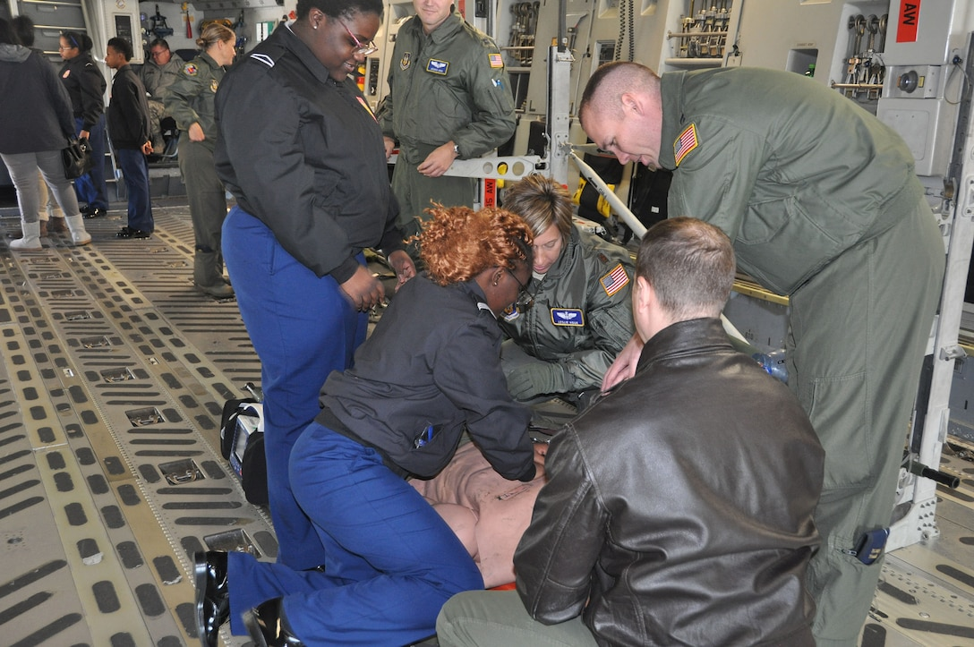 Airmen from the 445th Aeromedical Evacuation Squadron show two Meadowdale High School students how to do chest compressions on a simulated patient onboard a 445th Airlift Wing C-17 Globemaster III Oct. 18, 2018.