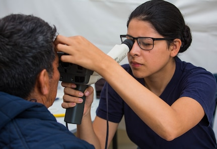 Hospitalman Stacy Rodriguez, from Covina, Calif., performs an eye exam on a patient at one of two medical sites.