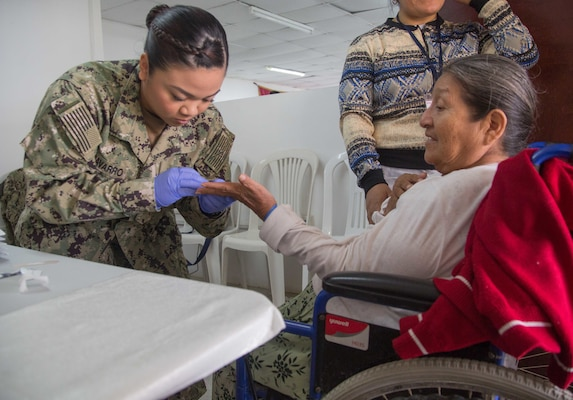 Hospital Corpsman 3rd Class Makhazandra Navarro, from Seattle, draws blood from a patient for laboratory testing at one of two medical sites.