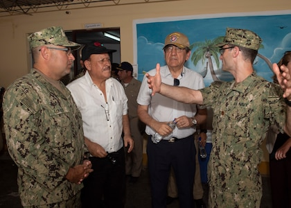 Lt. Cmdr. Peter McIntyre (right), the officer in charge of a medical site, explains the medical services provided to Jorge Castillo (center-right), Chairman of Defense of Peru, and Sergio Davila, a representative of the defense counsel of Peru, while Lt. Cmdr. Gustavo Lores translates.