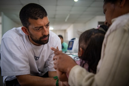 Aldo Buffa, a member of Cascos Blancos of Argentina, prescreens a patient at one of two medical sites.