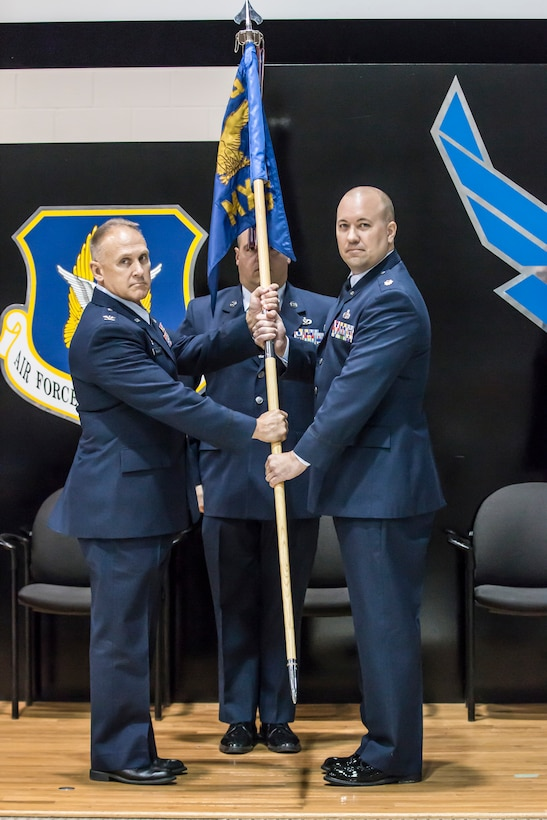 Col. Jay Smeltzer, 445th Maintenance Group commander, passes the guidon to the incoming 445th Maintenance Squadron commander, Maj. Randolph Gantt, during the 445th MXS change of command ceremony Oct. 13, 2018.