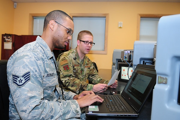 Staff Sgt. Wiggin Bernadotte, a cyber warfare operator in the Washington Air National Guard's 262nd Cyberspace Operations Squadron, works with Capt. Benjamin Kolar, a cyberspace operations officer in the 262nd, on an electrical substation simulator on Nov. 3, 2018. The 262nd is supporting Washington State Secretary of State Kim Wyman to help secure and protect voting systems for the 2018 election.