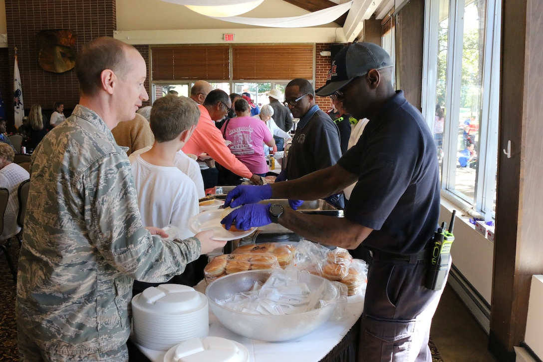 Lt. Col. Daniel Watson, Judge Advocate from Tyndall Air Force Base, left, receives his complimentary lunch from Arnold Air Force Base Fire and Emergency Services Driver/Operator Anthony Jimcoily during the Military Appreciation: Past, Present and Future Picnic, held Oct. 12 at Arnold Lakeside Center. The annual event is held to show appreciation to past and present service members and their families. Pictured to Jimcoily's right is Arnold AFB firefighter Thomas King. (U.S. Air Force photo by Bradley Hicks)