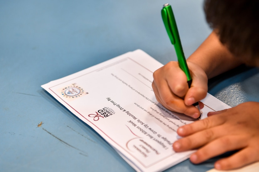 A kid fills out a Red Ribbon Week drug free pledge card Oct. 23, 2018 at the Joint Base Charleston, S.C., youth center.