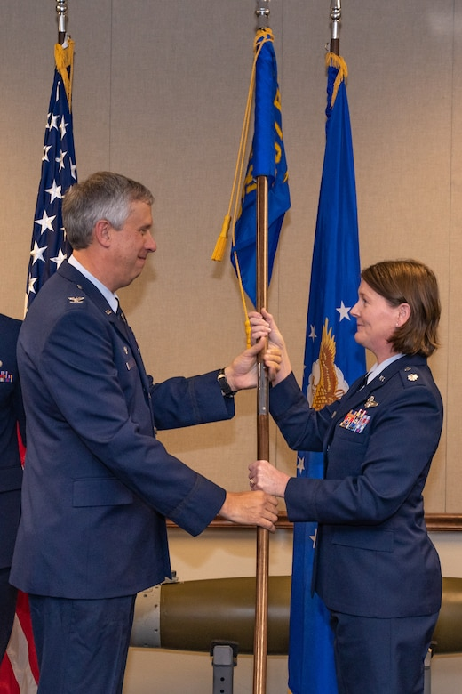 U.S. Air Force Col. Robert Burgess, 307th Operations Group commander, hands the 307th Operations Support Squadron guidon to Lt. Col. Joanna Mitchell during a change of command ceremony at Barksdale Air Force Base, Louisiana, Oct. 3, 2018.  Mitchell took command of the 307th OSS during the ceremony. She has served more than 20 years in the Air Force and has 2,132 flight hours. (U.S. Air force photo by Tech. Sgt. Cody Burt)