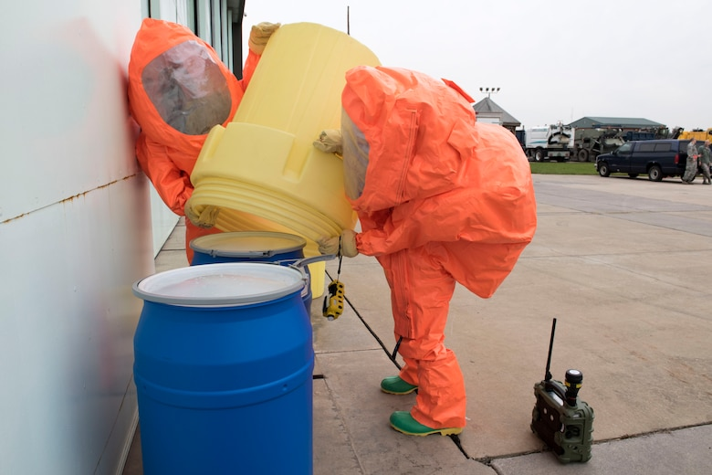 Master Sgt. Thomas Mucher and Tech. Sgt. Jennifer Blood, 167th Airlift Wing emergency management office, place an overpack container on a drum during a hazardous material training exercise at the 167th AW, Oct. 26, 2018. (U.S. photo by Senior Master Sgt. Emily Beightol-Deyerle)