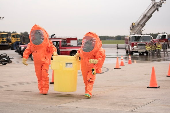 Master Sgt. Thomas Mucher and Tech. Sgt. Jennifer Blood, both assigned to the167th Airlift Wing emergency management office, donned in level-A hazmat suits, carry overpack containers during a hazardous material exercise at the Martinsburg, W.Va. air base, Oct. 26. (U.S. Air National Guard photo by Senior Master Sgt. Emily Beightol-Deyerle)