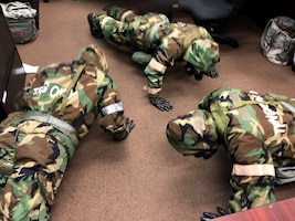 Airmen from the 104th Fighter Wing work in Mission Oriented Protective Posture level four Nov. 4, 2018, at Barnes Air National Guard Base, Massachusetts. The airmen kept morale high while working to enhance mission readiness.  (U.S. National Guard photo by 2Lt. Amelia Leonard. Cleared for public release)