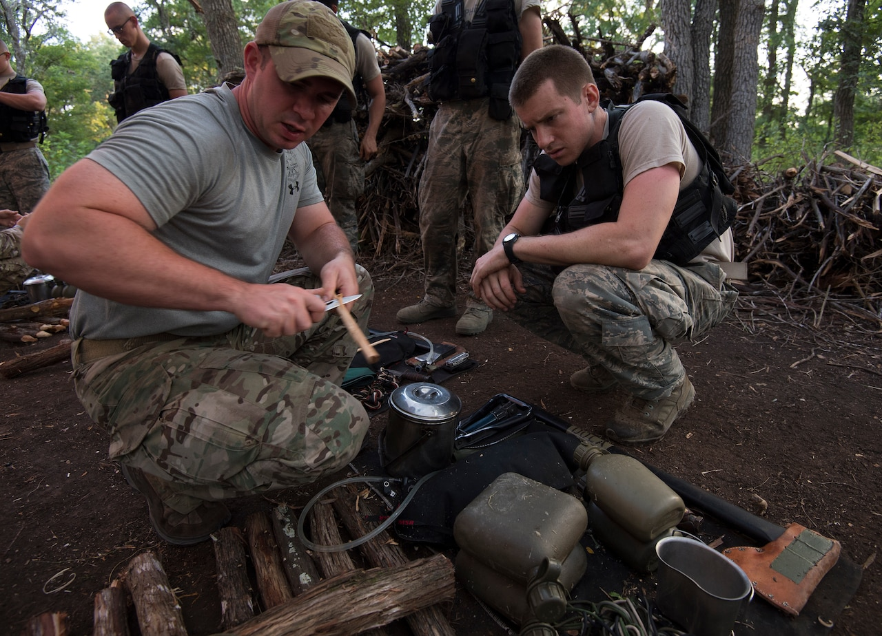 Airman carves spoon while other airman watches